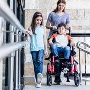 Mother walking with daughter and handicapped son